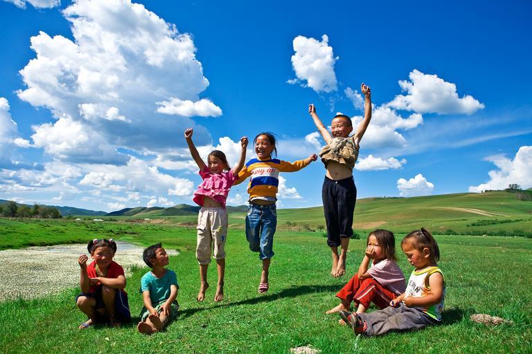 děti na zelené louce, některé vyskakují do vzduchu, jiné sedí na trávě.jpg