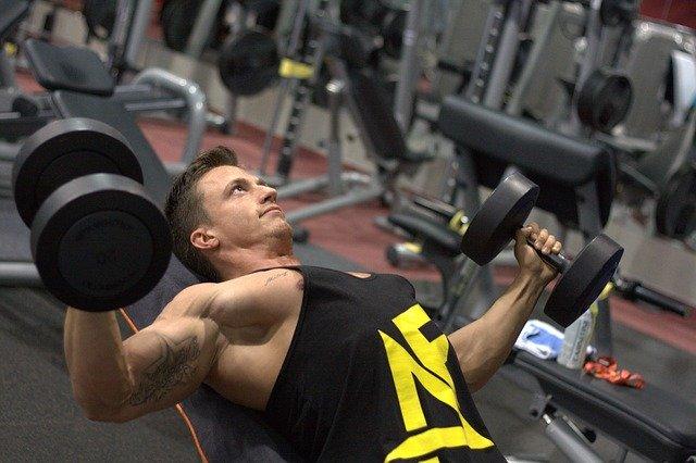 muž cvičí v posilovně s činkami